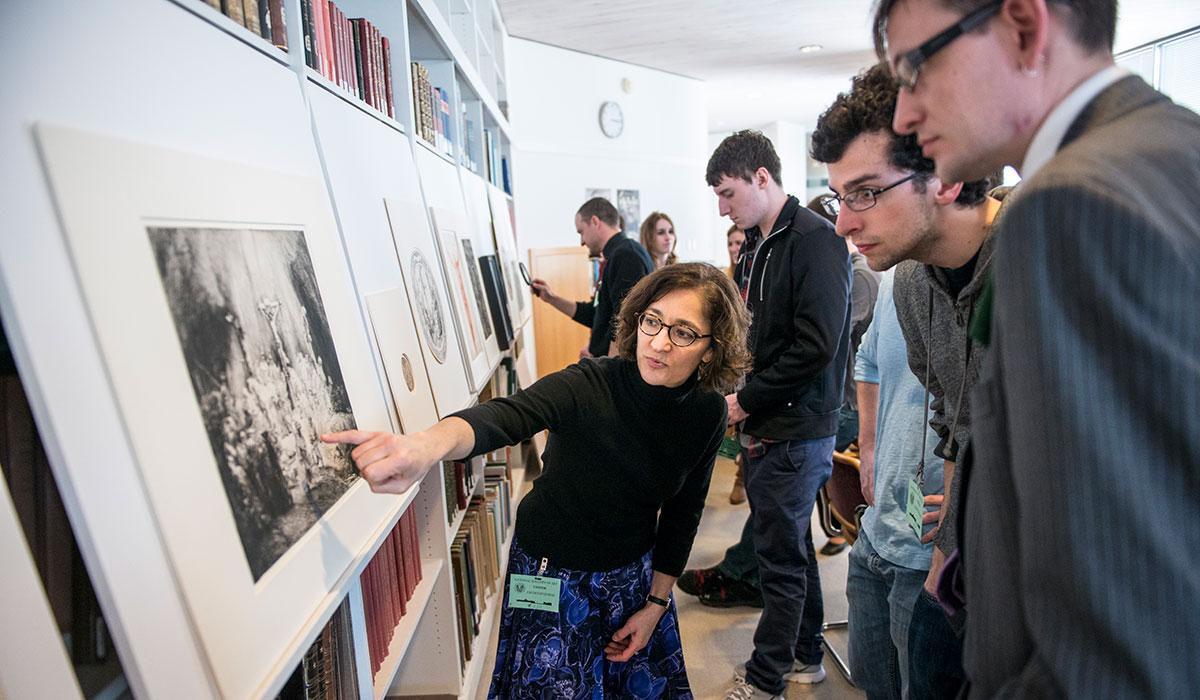 Professor Heimann pointing to artwork