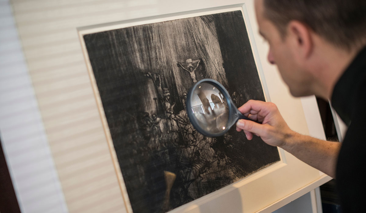Student studying piece of art with magnifying glass